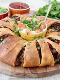 Taco ring with crescent rolls on wood cutting board with ramekins of sour cream, salsa and guacamole