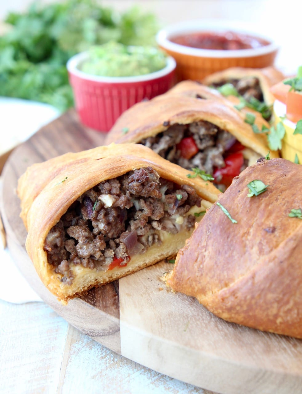 Taco ring with crescent rolls filled with ground beef, onions and peppers on wood cutting board with piece sliced out