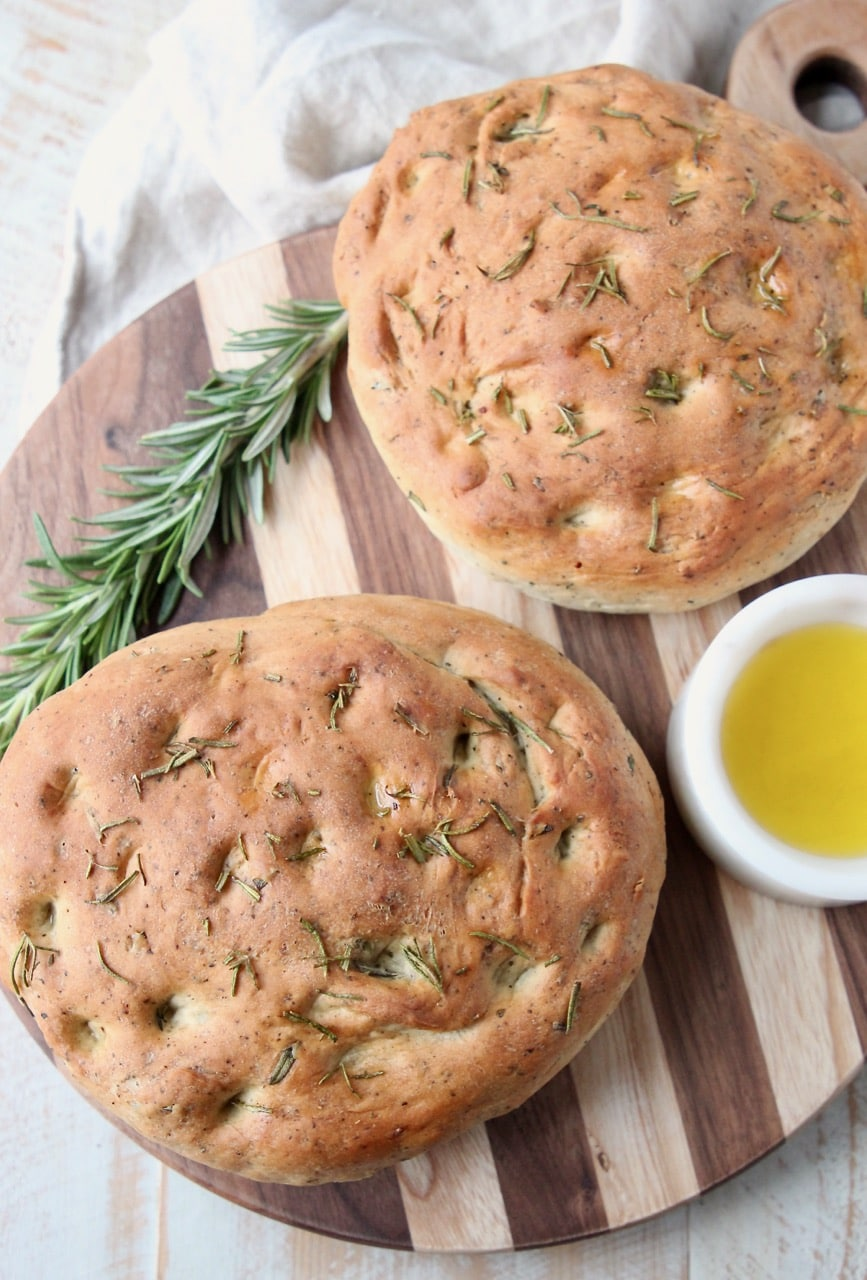 Two loaves of rosemary focaccia bread on wood cutting board with fresh sprig of rosemary and small white bowl of olive oil
