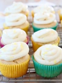Lemon cupcakes with cream cheese frosting sitting on wire cooling rack