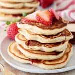 Strawberry pancakes stacked on plate with fresh strawberry slices