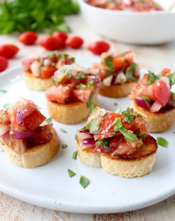 tomato bruschetta on plate, topped with fresh chopped basil
