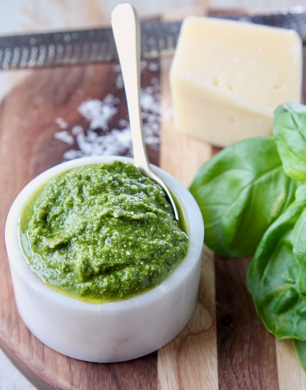 Basil pesto in small white bowl sitting next to fresh basil leaves and a block of parmesan cheese
