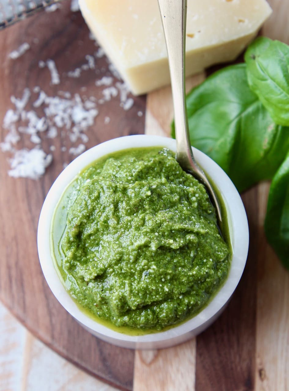 Overhead shot of basil pesto in a small white bowl with a small gold spoon in the bowl