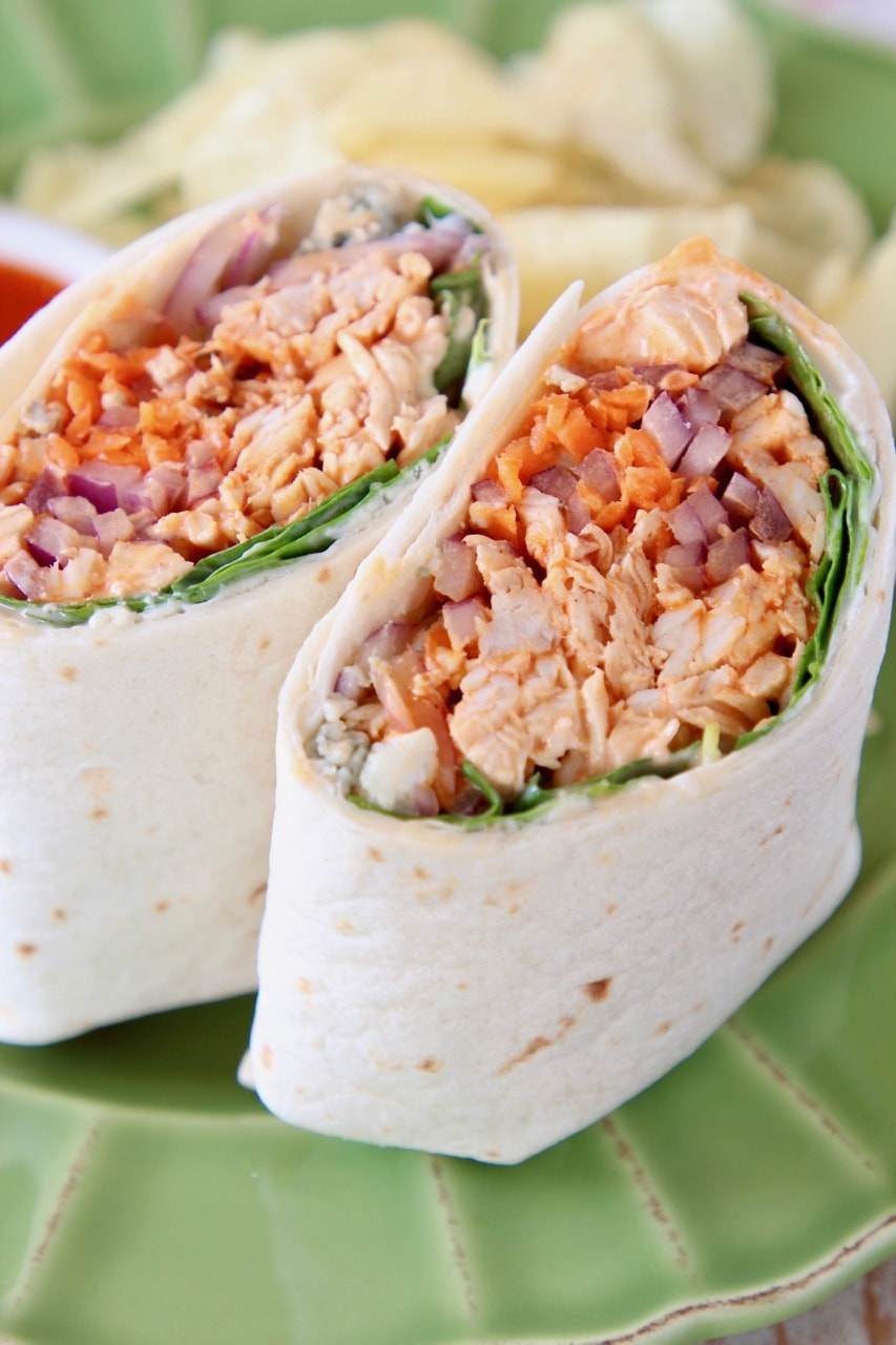 Buffalo chicken wrap sliced in half on green plate