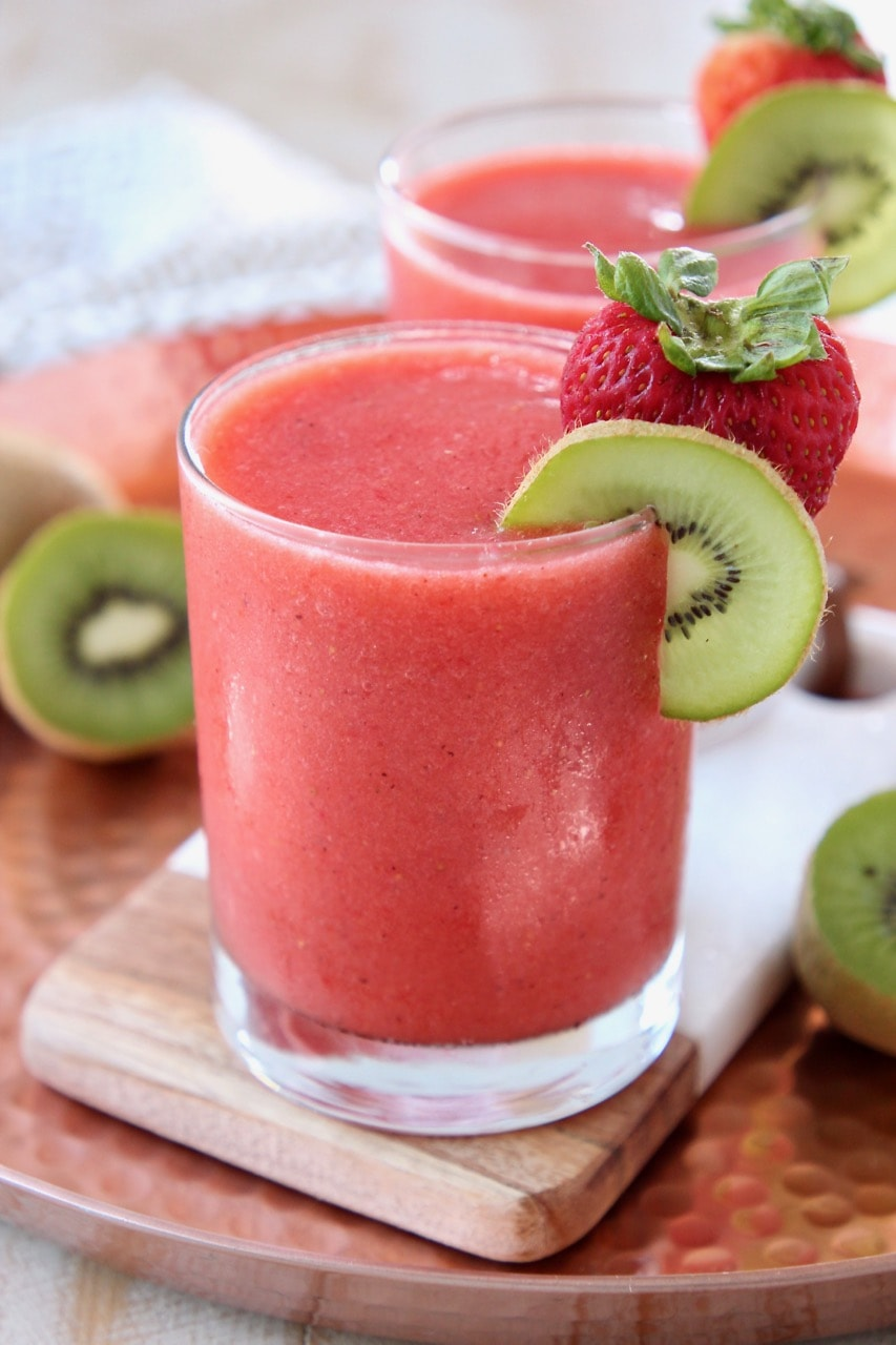 Strawberry slushie in glass with strawberry and kiwi slice on the rim of the glass