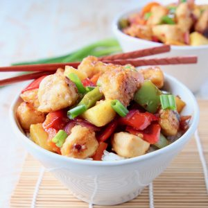 Sweet and sour chicken with bell peppers and pineapple chunks in bowl with chopsticks