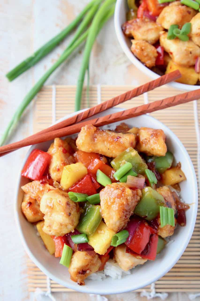 Sweet and sour chicken with pineapple and bell peppers on top of rice in bowl with chopsticks on the side