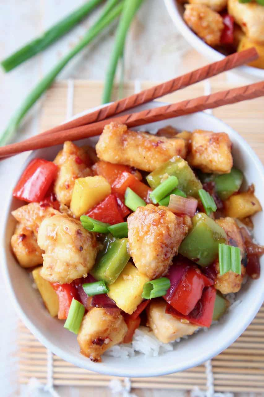 Sweet and sour chicken in bowl with chopsticks and green onions