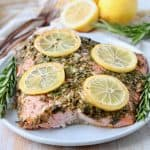 Baked salmon on plate with lemon slices and rosemary sprigs