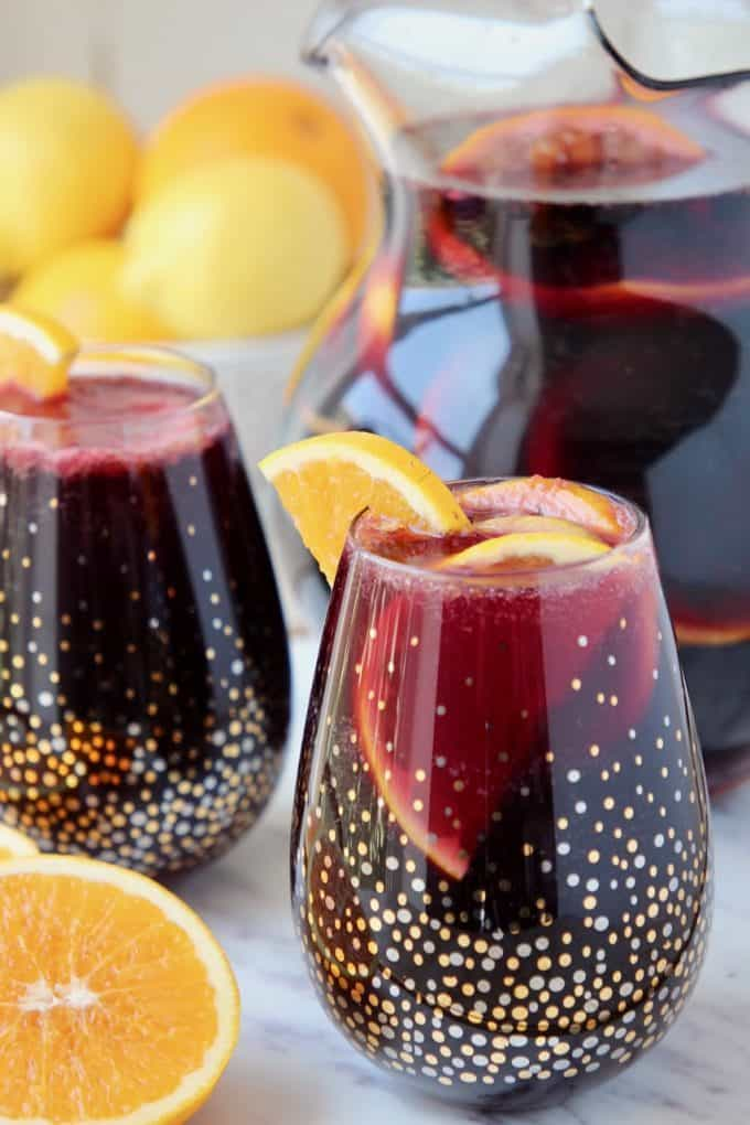 Red sangria in glasses and pitcher with oranges