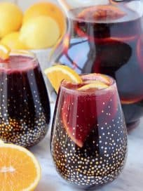 Red sangria in glasses and pitcher with sliced oranges