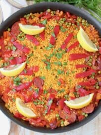 Overhead image of spanish paella in skillet with lemon wedges on top