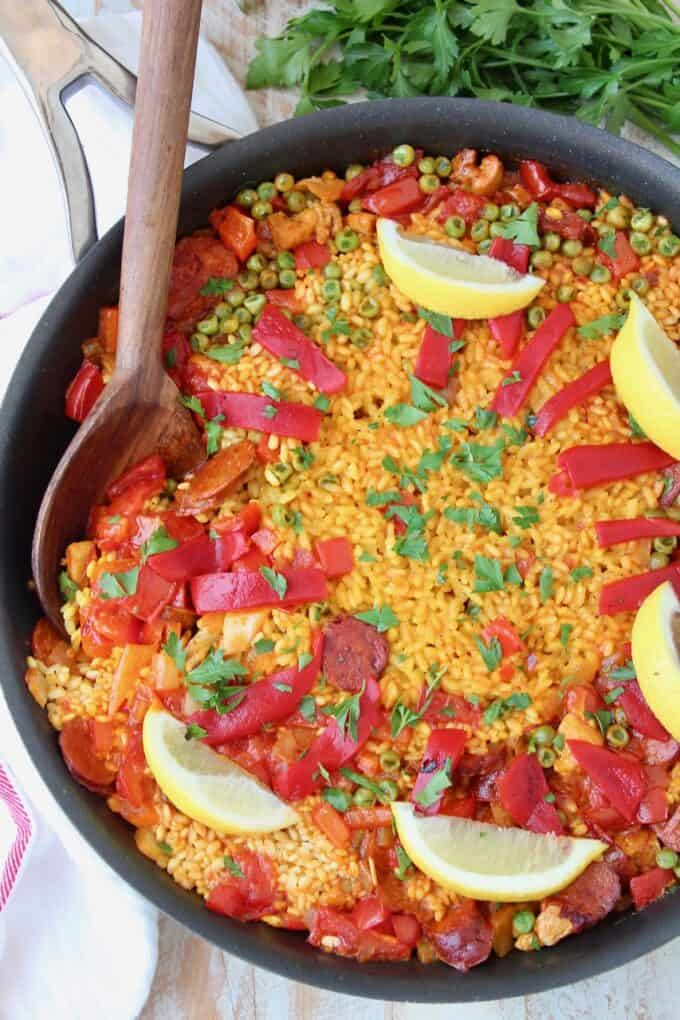Overhead image of paella in skillet with wooden serving spoon