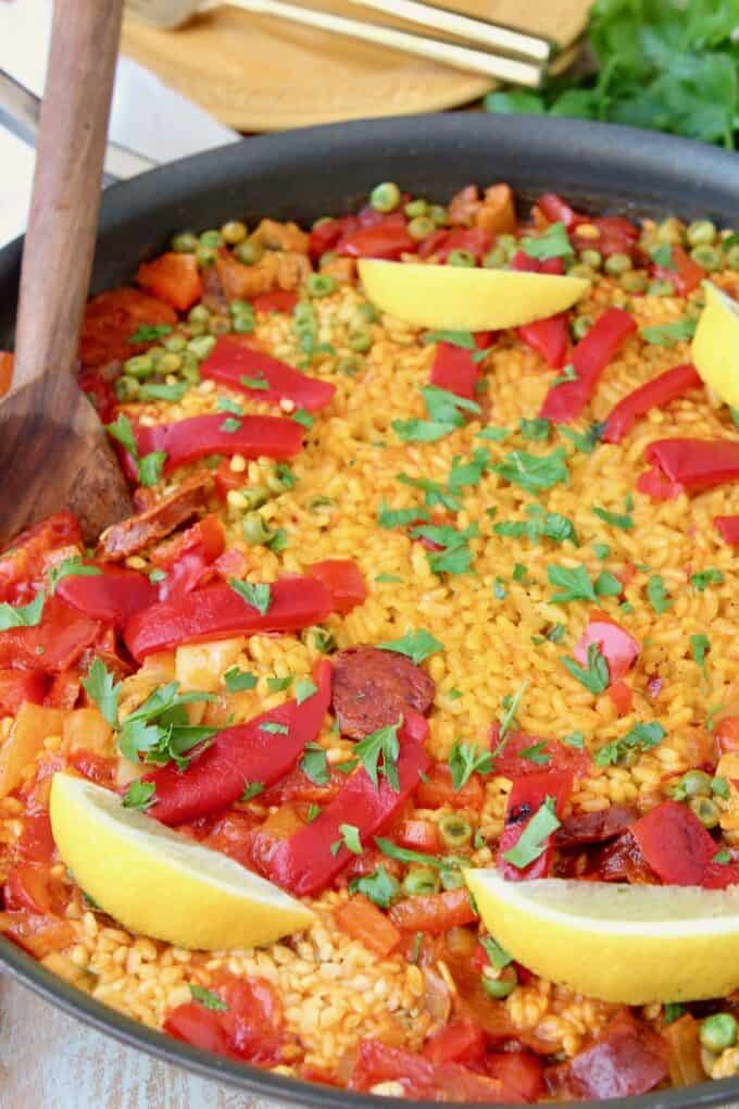 Pan of spanish paella topped with lemon wedges