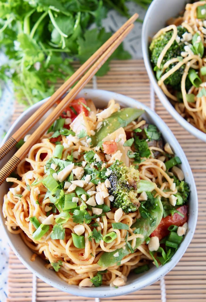 Noodles and vegetables in bowl with chopsticks on the edge of the bowl