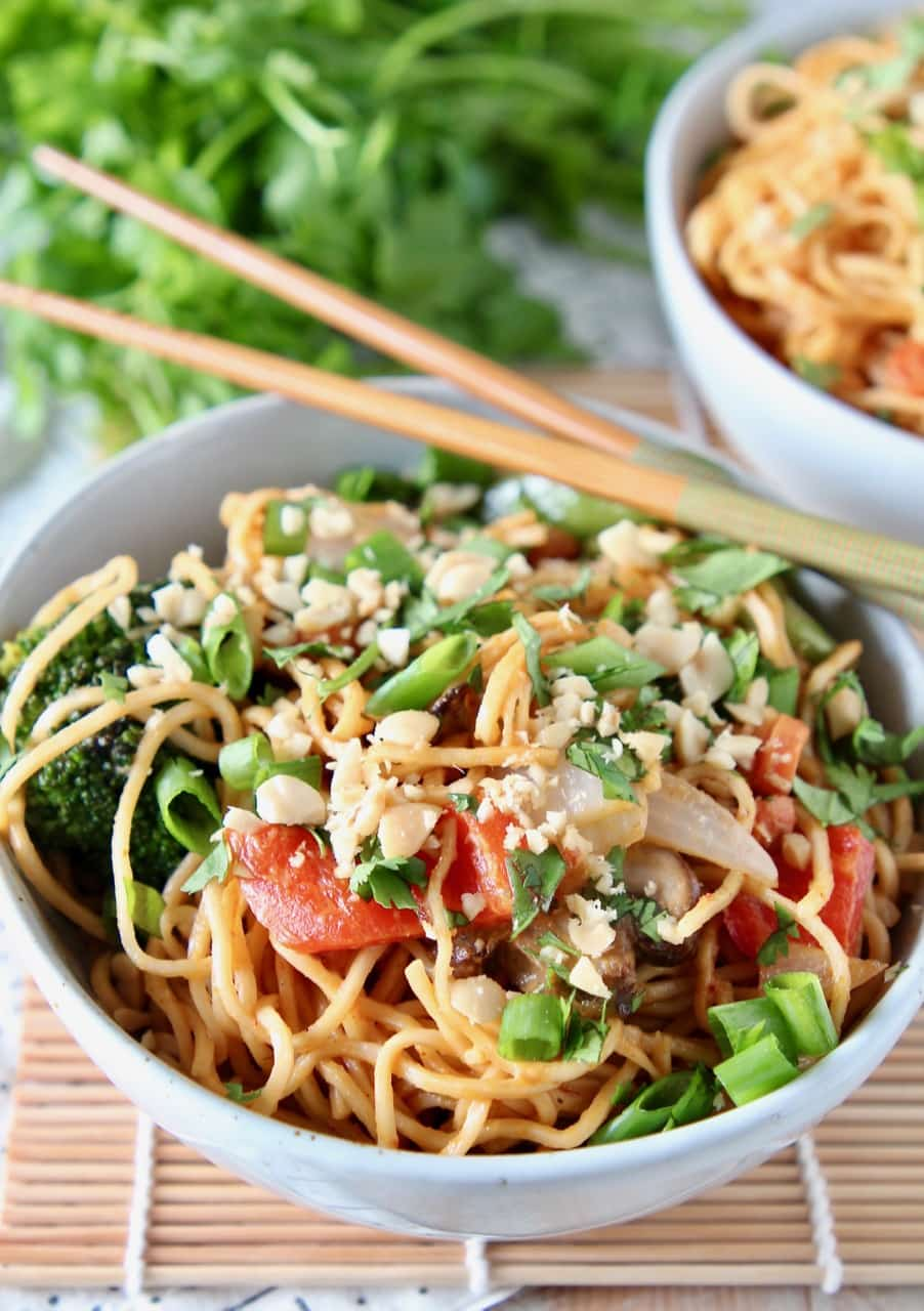 Ramen noodles and vegetables tossed with Thai peanut sauce in bowl with chopsticks on the side