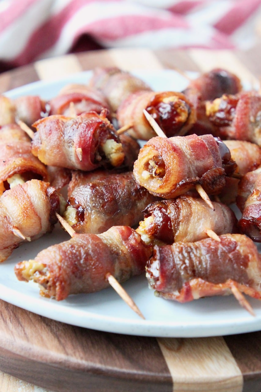 Bacon wrapped dates piled up on white plate on top of wood cutting board
