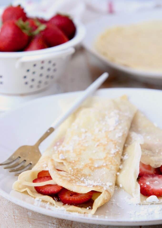 Nutella strawberry filled crepes on plate with fork