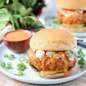 Chicken burger on bun with blue cheese crumbles and buffalo wing sauce