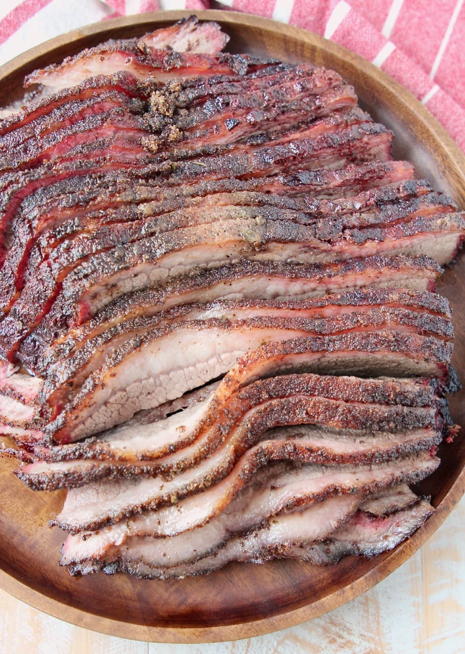 Overhead shot of sliced brisket on round wood serving tray