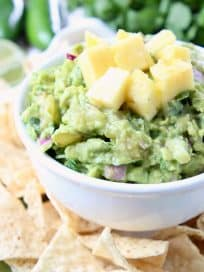 Guacamole in white bowl topped with diced pineapple