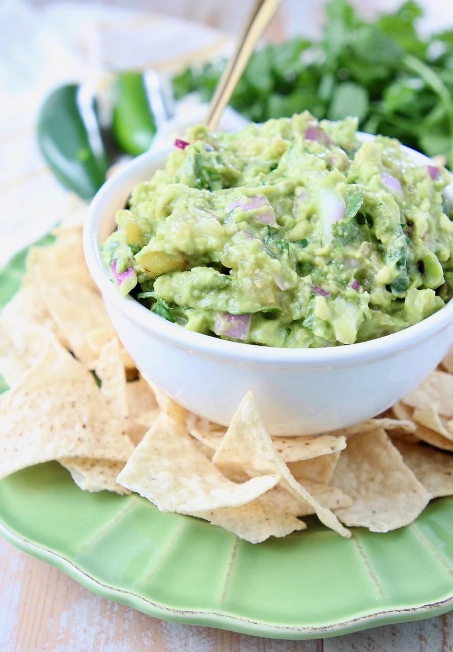 Tomatillo guacamole in white bowl on green plate, surrounded by tortilla chips
