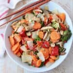 Overhead image of roasted Asian vegetables in white bowl with chopsticks on the side
