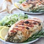 grilled chicken breast on plate with rosemary sprigs and lemon wedges