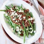 Overhead image of fresh green beans in serving bowl with pecans and blue cheese