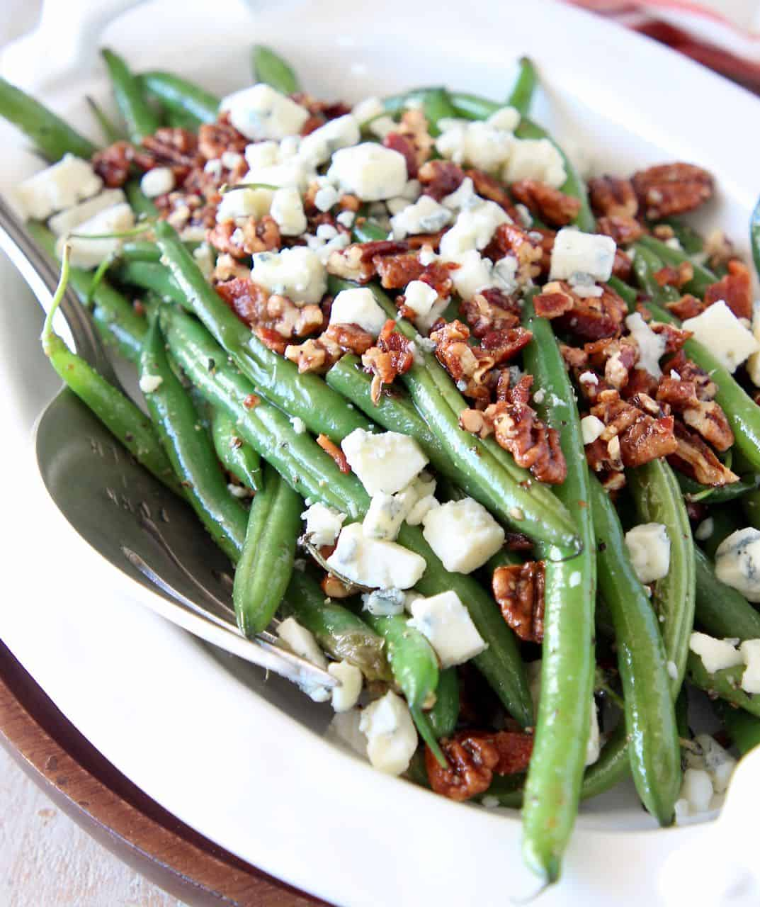 Fresh cooked green beans in serving bowl topped with crumbled bacon, pecans and blue cheese