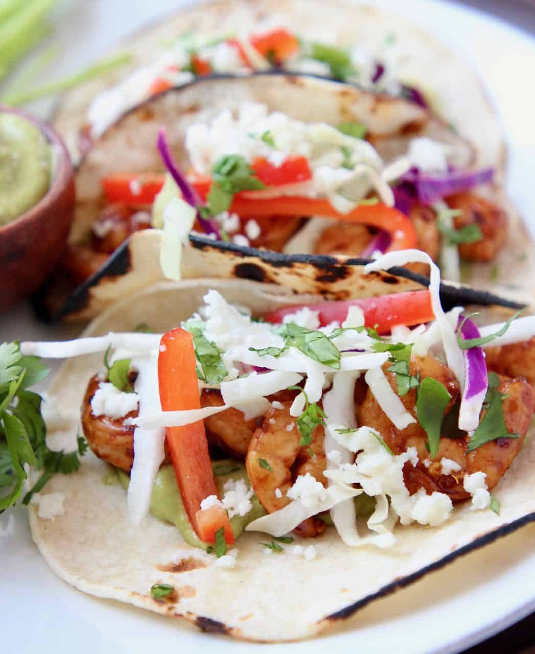 Grilled shrimp tacos, topped with slaw on white plate