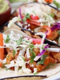 Grilled shrimp tacos in corn tortillas topped with slaw and cotija cheese