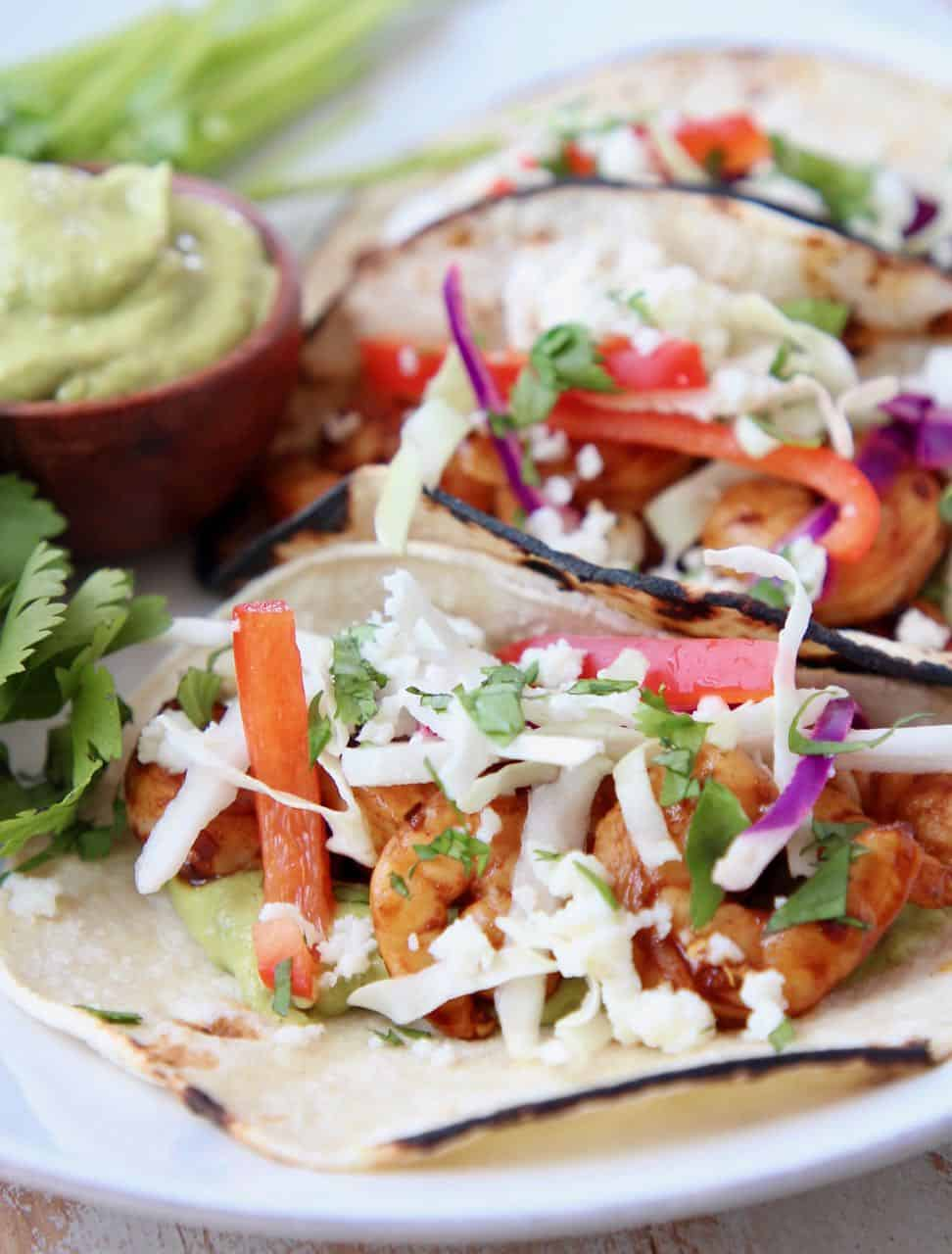 Tacos filled with shrimp, slaw and avocado salsa on white plate with fresh cilantro