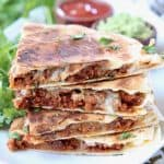 Stacked up slices of soy chorizo quesadilla on plate