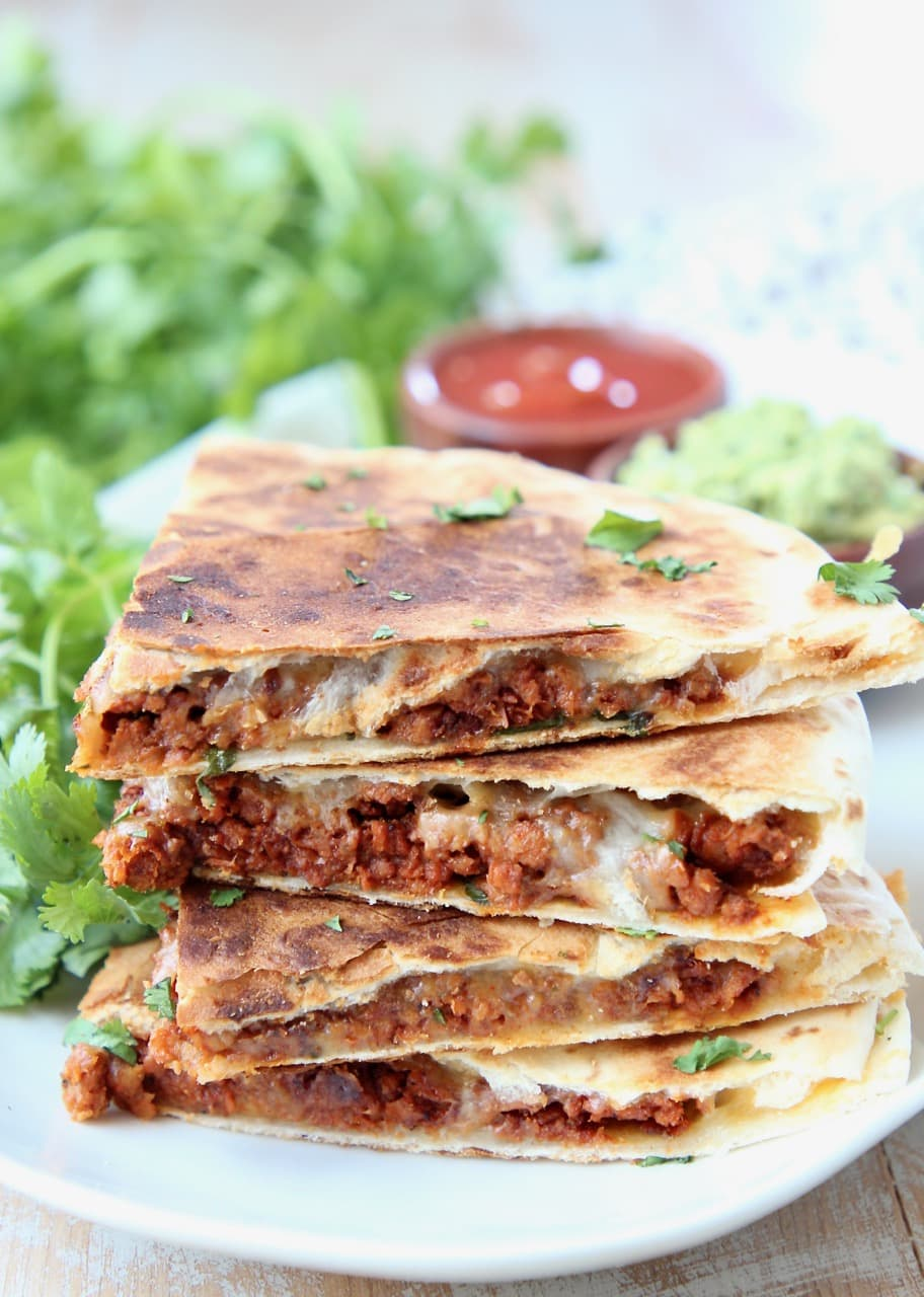 Soy chorizo quesadilla slices stacked up on a plate with fresh cilantro