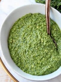 Kale pesto in white bowl with copper spoon