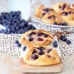 Blueberry Pastries sitting on cutting board on top of gold and white patterned towel with a white colander of blueberries spilling on in the background next to a plate of blueberry pastries