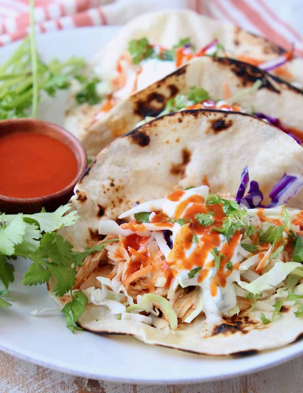Tacos on plate with slaw and buffalo sauce