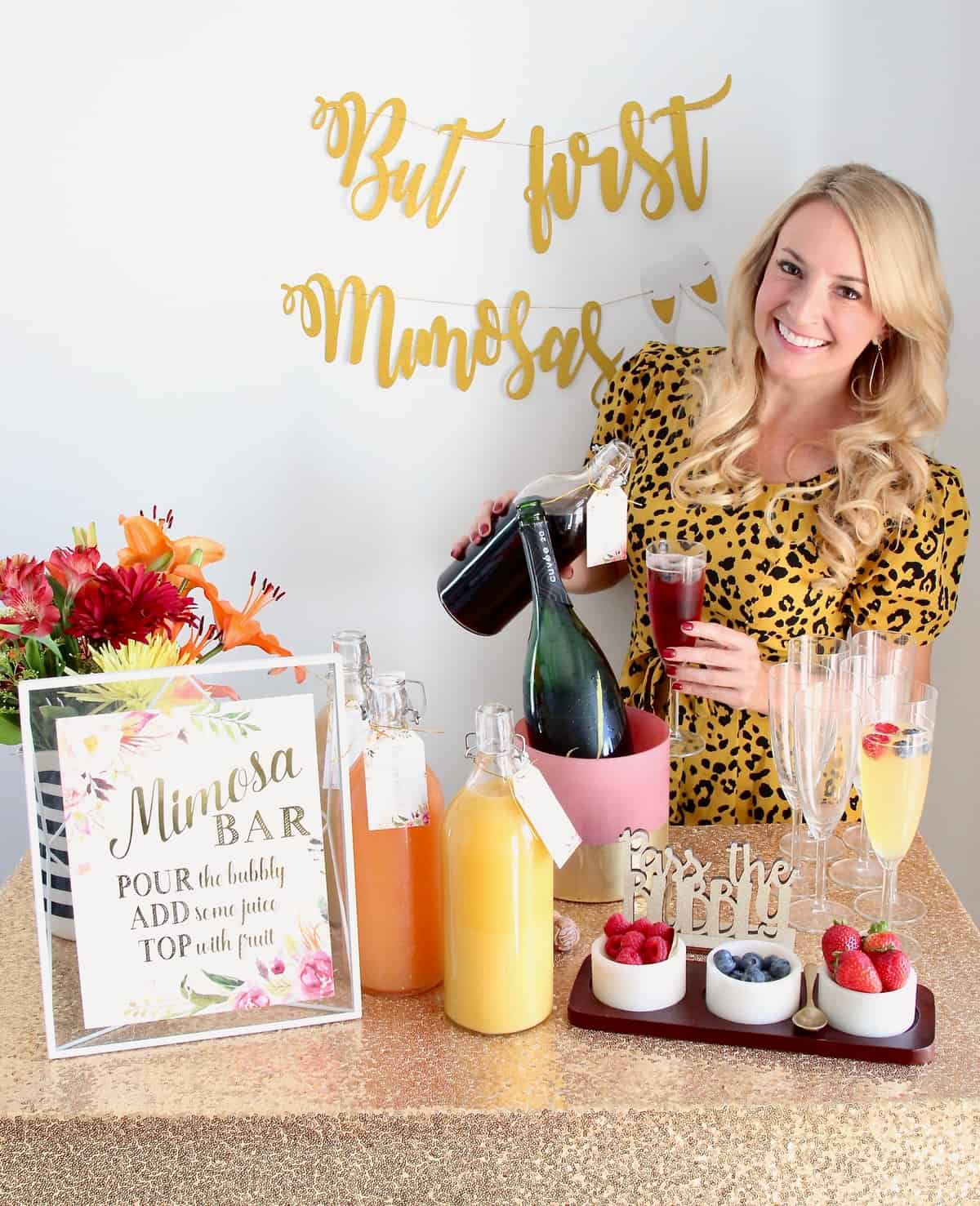 Woman pouring juice into a mimosa standing behind a mimosa bar