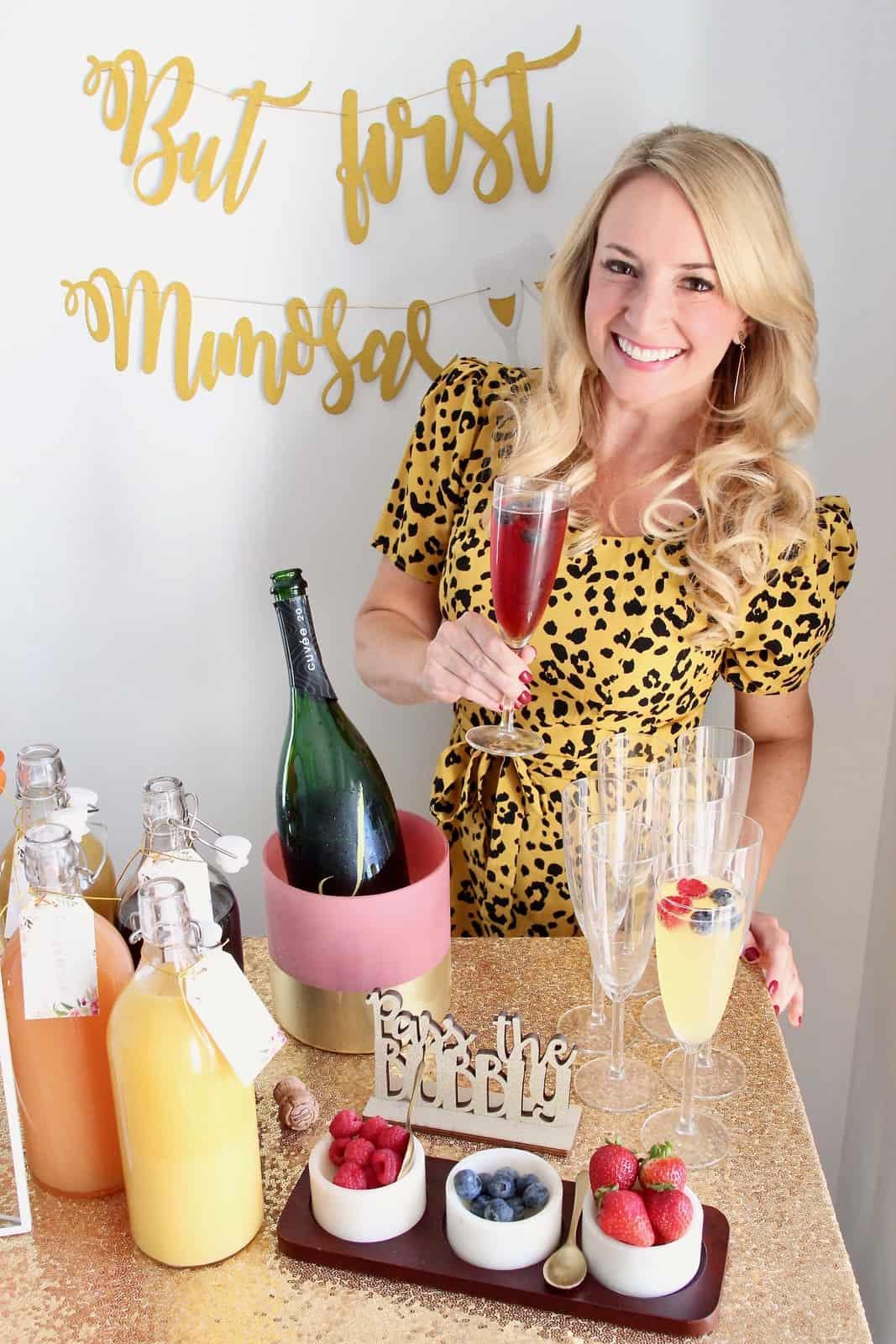 Woman holding mimosa standing behind mimosa bar