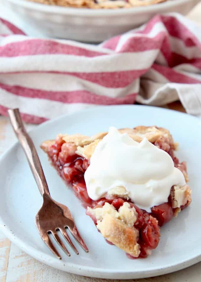 piece of pie on plate topped with whipped cream