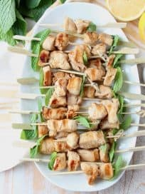 Overhead shot of chicken skewers on white plate