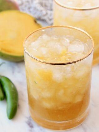 margaritas in glasses next to fresh sliced mango