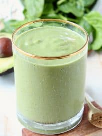 Green smoothie in glass, sitting next to an avocado half and fresh spinach