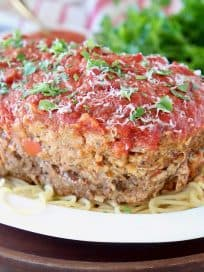 Italian Meatloaf sitting on large bowl of spaghetti noodles with fresh parsley on top