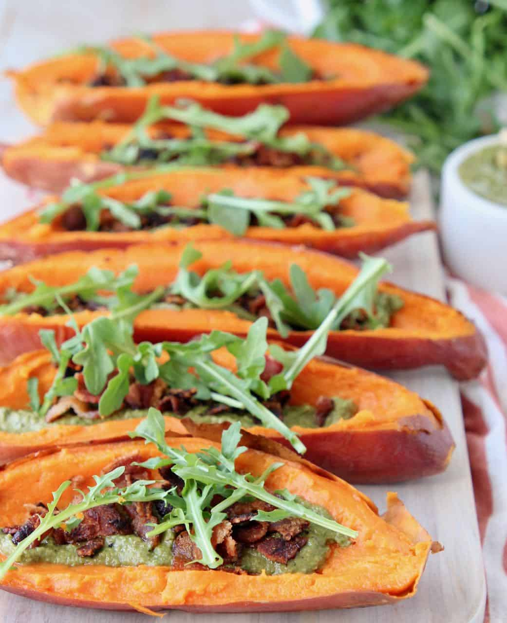 Sweet potato skins topped with arugula on wood cutting board
