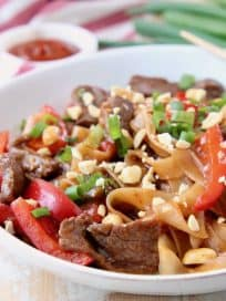 Kung pao beef, rice noodles, green onions and sliced red bell peppers in large white bowl