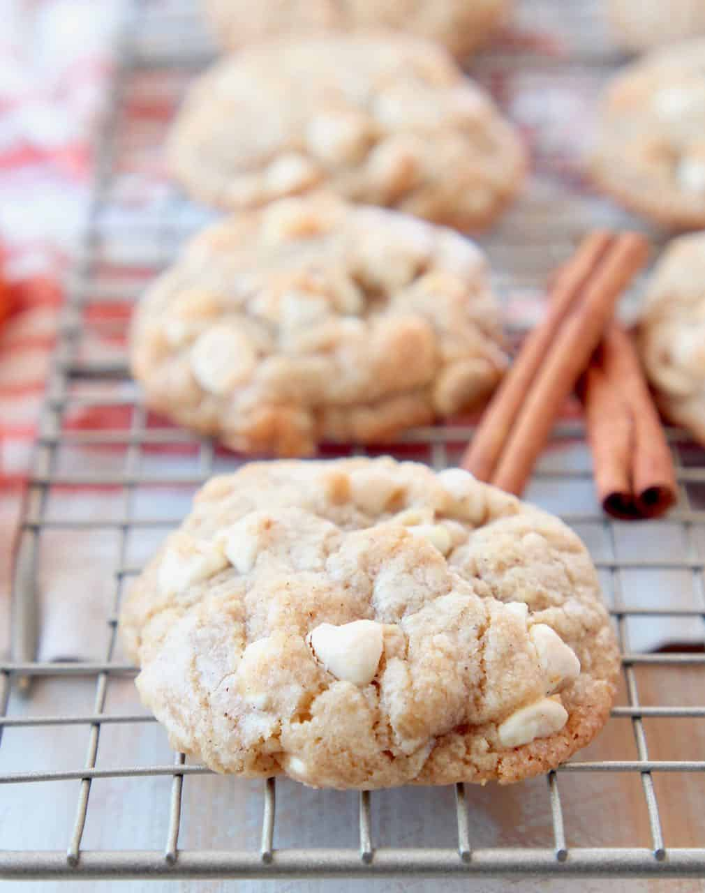 White chocolate chip cookies on wire baking rack with cinnamon sticks