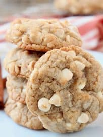 Pumpkin spice white chocolate chip cookies stacked up on a plate